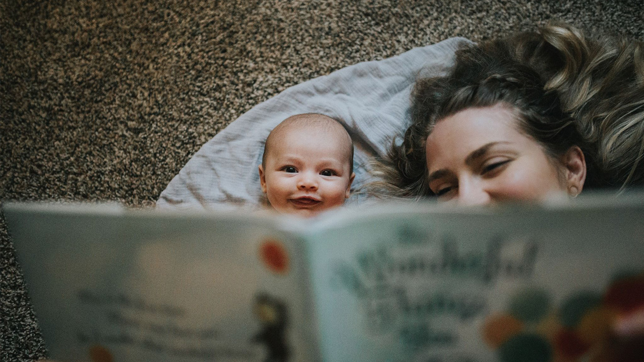 mother reads to a baby